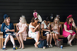 © Licensed to London News Pictures. 19/06/2018. London, UK. A group of Racegoers enjoy a lunch break at day one of Royal Ascot at Ascot racecourse in Berkshire, on June 19, 2018. The 5 day showcase event, which is one of the highlights of the racing calendar, has been held at the famous Berkshire course since 1711 and tradition is a hallmark of the meeting. Top hats and tails remain compulsory in parts of the course. Photo credit: Ben Cawthra/LNP