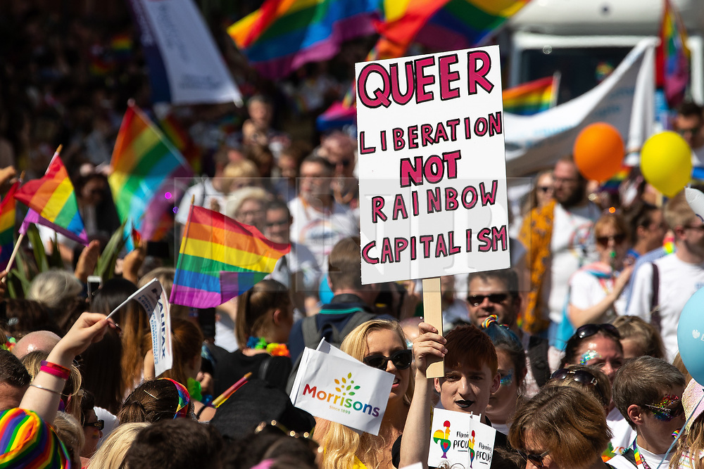 """© Licensed to London News Pictures . 05/08/2018. Leeds, UK. Anti-capitalist """" Queer Liberation not rainbow Capitalism """" placard . Leeds Gay Pride parade through the Yorkshire city's centre . Leeds's annual Gay Pride festiva celebrates the city's LGBTQ+ life and culture . Photo credit: Joel Goodman/LNP"""