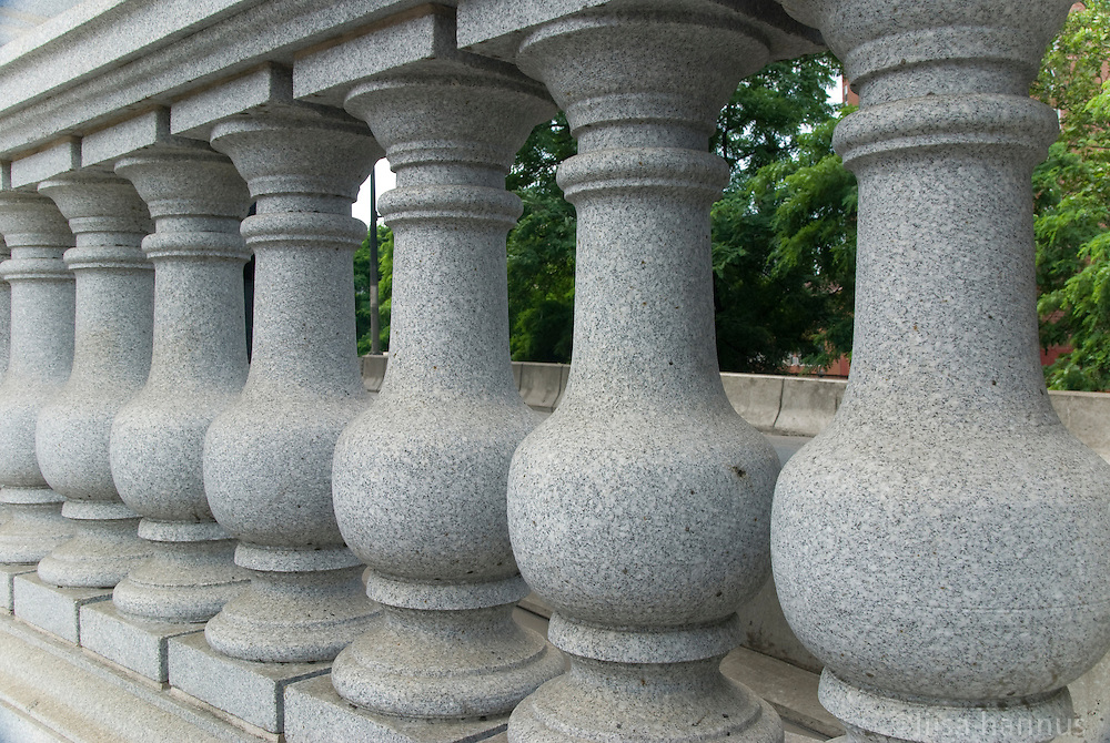 Stone balusters along the plaza at the Manhattan Bridge, with teres in the background in Manhattan, New York City