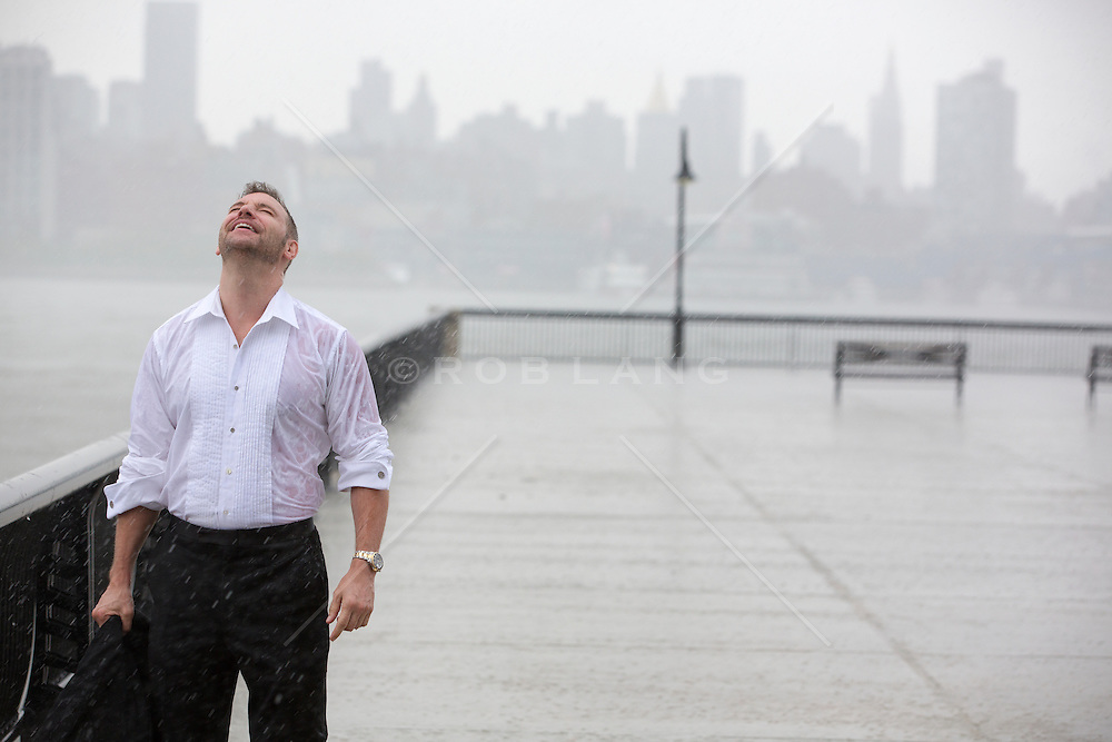 handsome middle aged man in a tuxedo shirt standing on a pier in Hoboken, NJ in the rain.