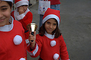 Children dressed up as Santa Claus in a parade in Wadi Nisnas, Haifa, Israel during the Holiday of holidays festival, celebrating Hanuka-Christmas-Ramadan festival in the Haifa Neighbourhood of Wadi Nisnas