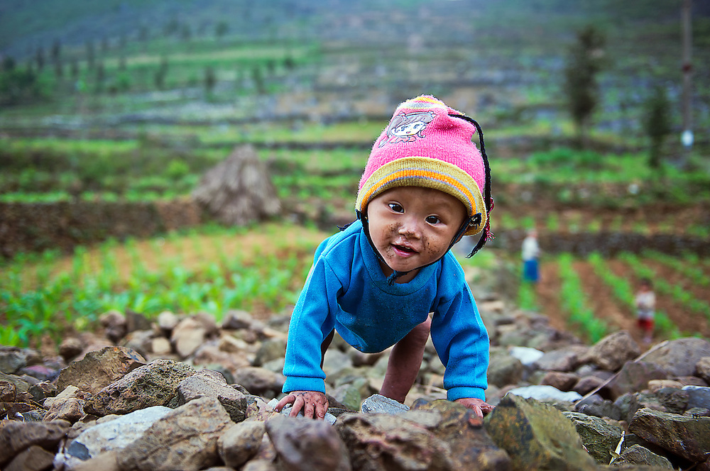 A toddler waits for mum and dad working in the corn fields near Meo Vac, Vietnam.