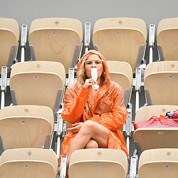 A spectator enjoys some champagne in the rain during Day 3 of the French Open 2018 on May 29, 2018 in Paris, France. (Photo by Dave Winter/Icon Sport)