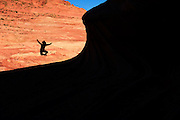 A female hiker jumps for joy after having made the hike in to The Wave in the Coyote Buttes North special permit area of the Vermillion Cliffs wilderness area on the border with Utah and Arizona. This amazing, unique and fragile landscape is remote and heavily regulated