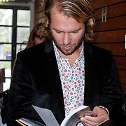 NLD/Amsterdam/20121029 - Boekpesentatie 'Het alles is Familie Kookboek', Thijs Romer bekijkt het boek