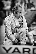 1967 Formula One World Champion, Denny Hulme takes a moment to gather his thoughts before qualifications begin for the 1972 United States Grand Prix at Watkins Glen. He always seemed his quickest when he was at peace. It was the end of a long 1972 season that saw New Zealand's Hulme's McLaren again finish 3rd in the World Championship. <br />