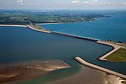 Nederland, Zuid-Holland, Haringvliet, 12-06-2009; Haringvlietsluizen en Haringvlietdam, gezien naar Rockanje op het eiland Voorne-Putten, onder in beeld de damaanzet op Goeree-Overflakkee. Aan de horizon Rotterdam Europoort. De sluizen, onderdeel van de Deltawerken, zijn spuisluizen en zorgen er voor dat het zoete water uit het Haringvliet (rechts op de foto) zoals aangevoerd door Maas en Rijn geloosd kan worden. In het kader van modern natuurbeheer  ('getemd getij') gaan de sluizen tegenwoordig bij eb én vloed beperkt open, om de getijden hun enigszin terug te laten komen in achterliggende estuarium .Dam and sluices between islands Voorne-Putten en Goeree-Overflakkee (bottom); the sluices are for draining water coming from the rivers Rhine and Maas (Meuse) from the natural bassin (right) to the North sea (left). Modern ecological insight has led to opening the sluices semi-permanently, resulting in the estuary function of the Haringvliet patially being restored.Swart collectie, luchtfoto (25 procent toeslag); Swart Collection, aerial photo (additional fee required).foto Siebe Swart / photo Siebe Swart