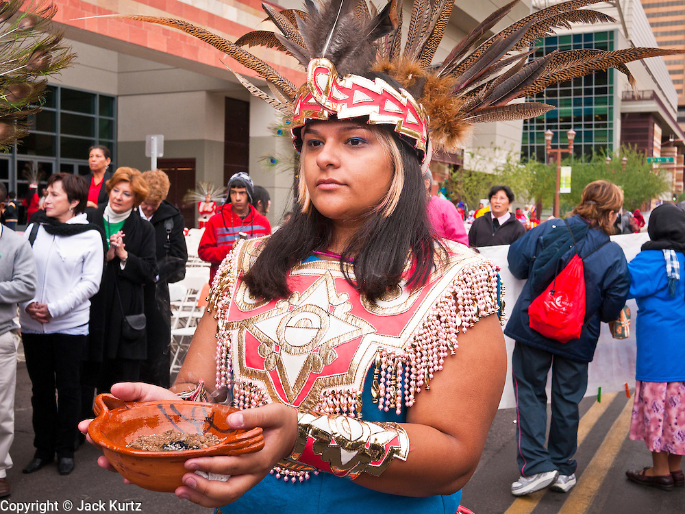 "03 DECEMBER 2011 - PHOENIX, AZ:    A woman carries incense during a procession to honor the Virgin of Guadalupe in Phoenix Saturday. The Phoenix diocese of the Roman Catholic Church held its Sixth Annual Honor Your Mother Day Saturday to honor the Virgin of Guadalupe. According to Mexican Catholic tradition, on December 9, 1531 Juan Diego, an indigenous peasant, had a vision of a young woman while he was on a hill in the Tepeyac desert, near Mexico City. The woman told him to build a church exactly on the spot where they were standing. He told the local bishop, who asked for some proof. He went back and had the vision again. He told the lady that the bishop wanted proof, and she said ""Bring the roses behind you."" Turning to look, he found a rose bush growing behind him. He cut the roses, placed them in his poncho and returned to the bishop, saying he had brought proof. When he opened his poncho, instead of roses, there was an image of the young lady in the vision. The Virgin is now honored on Dec 12 in Catholic churches throughout Latin America and in Hispanic communitied in the US.  PHOTO BY JACK KURTZ"
