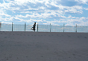 Child running through sand dunes on the beach