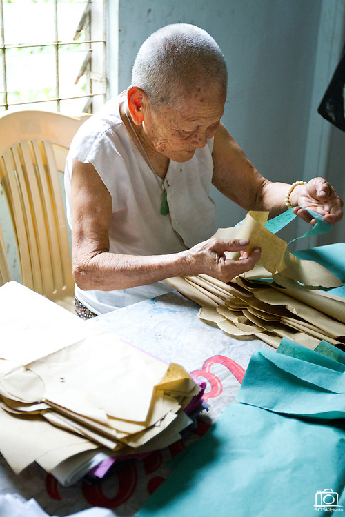 92 year old, Huong Phung makes paper clothes to burn for prayer at the Chua Dieu Vien Pagoda, Hue, Vietnam.  Photo by Stan Olszewski/SOSKIphoto
