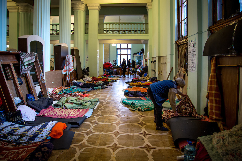 A woman makes a bed in the city hall, occupied by the protesters and partially transformed into dormitories.