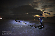 Guide dog sleds on a January afternoon as moon appears from cleairing clouds in the months-long polar night near Longyearbyen, Svalbard, Norway.