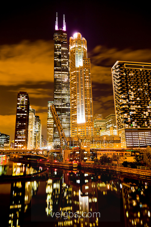 Colorful Chicago West Loop at Night with Willis Tower (formerly Sears Tower), Chicago River, and Congress Parkway bridge. Photo is vertical and high resolution.