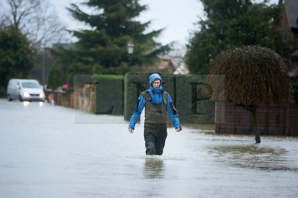 © London News Pictures. 11/02/2014. Wraysbury, UK.  A resident walking through flood water  in Wraysbury, Berkshire. The area has been hit hard by recent flooding from the nearby Thames River. Photo credit : Ben Cawthra/LNP