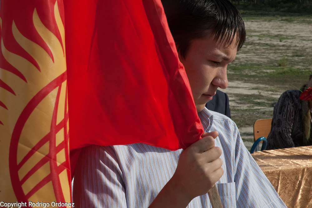 Dadahon Yadgarov, 17, parades the flag of the Kyrgyz Republic while the national anthem plays, during the ceremony to mark the 'first bell', or first day of school, at School 124 in Osh, Kyrgyzstan.