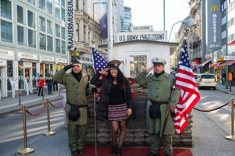 Tourists posing with American soldiers at Checkpoint Charlie in Berlin, Germany