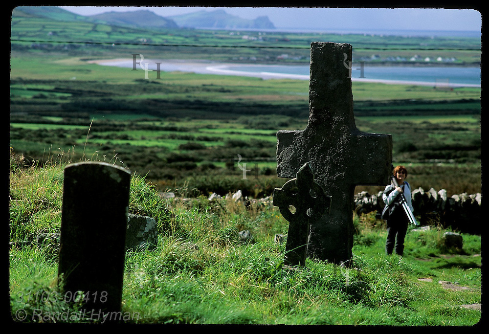 Woman photographer admires stone cross (7th-8th c.) and Celtic cross in Kilmalkedar Church cemetery; Dingle Peninsula, Ireland.
