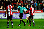 Referee James Linington is approached by Lloyd James (4) of Exeter City during the EFL Sky Bet League 2 match between Exeter City and Luton Town at St James' Park, Exeter, England on 17 October 2017. Photo by Graham Hunt.