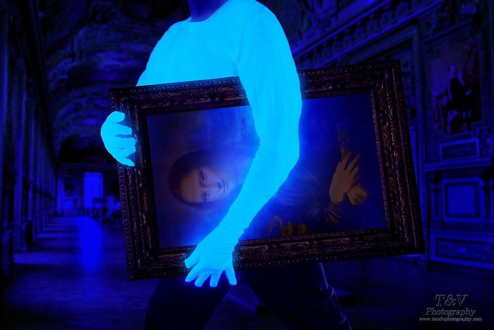 A thief wearing a glowing shirt and gloves carries the Mona Lisa through the Louvre at night.  Blacklight photography.