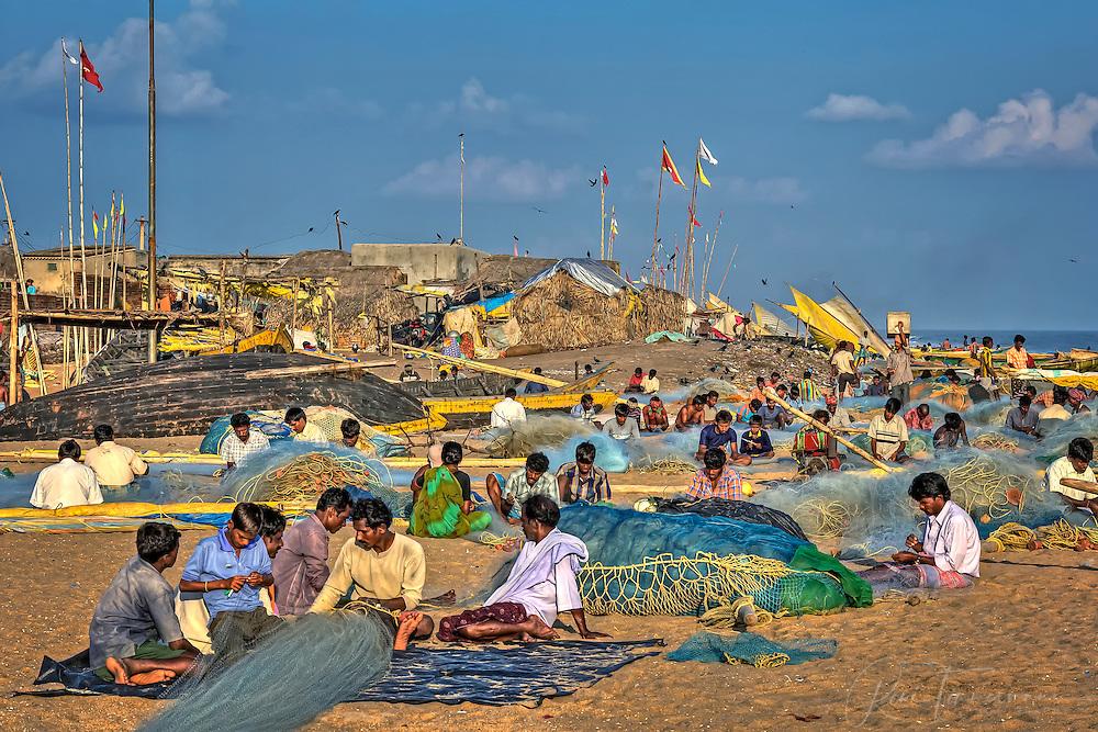 fishermen are reparing fishingnets on the beach