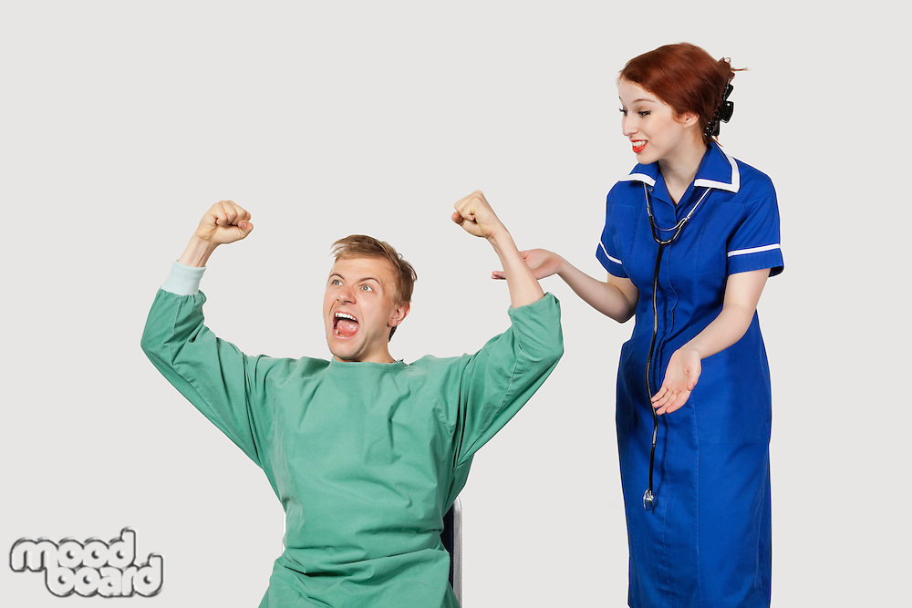 Young male patient with female nurse celebrating success against gray background
