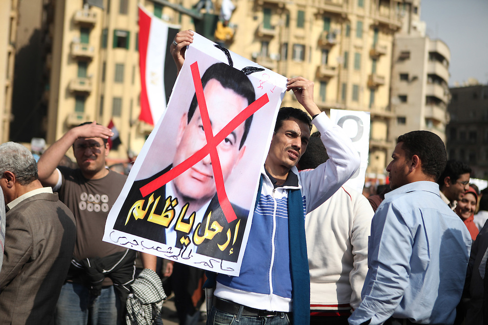 A protester holds an anti-Mubarak sign.