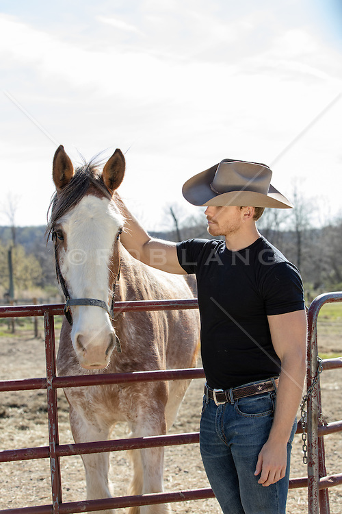 cowboy petting a horse on a ranch