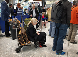 © Licensed to London News Pictures. 11/12/2017. London, UK. A passenger sits on a baggage trolley as she waits in line to check in at Heathrow's Terminal 5 after yesterday's snow continues to affect transport. British Airways had already cancelled 30 flights before 10am today. Photo credit: Peter Macdiarmid/LNP