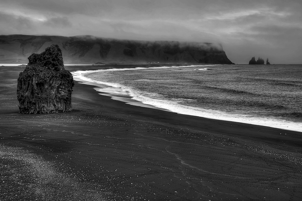 """The beautiful black sand beach of Reynisfjara includes the signature formation Reynisdrangar in the distance and Arnardrangur (""""Eagle rock"""") on the left."""