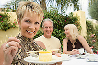 Woman eating dessert with friends outdoors