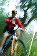 A young man mountain biking through a muddy field at Rabbit Mountain Open Space near Lyons, CO