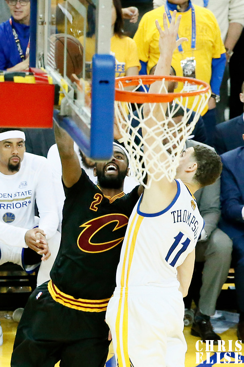 12 June 2017: Cleveland Cavaliers guard Kyrie Irving (2) goes for the layup against Golden State Warriors guard Klay Thompson (11) during the Golden State Warriors 129-120 victory over the Cleveland Cavaliers, in game 5 of the 2017 NBA Finals, at the Oracle Arena, Oakland, California, USA.