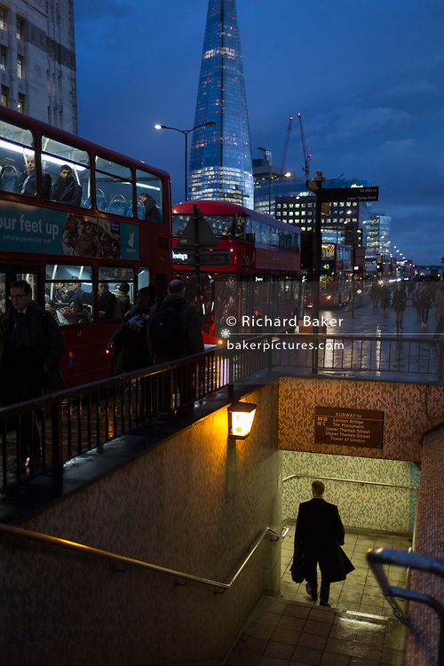 With the Shard in the background, pedestrians descend steps into the tunnel under London Bridge during the evening rush-hour, on 7th November 2018, in London, England.