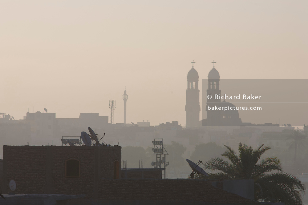 Looking East from the West Bank, early light over the River Nile and city of Luxor with its twin spires of the Christian Manak church, Nile Valley, Egypt.
