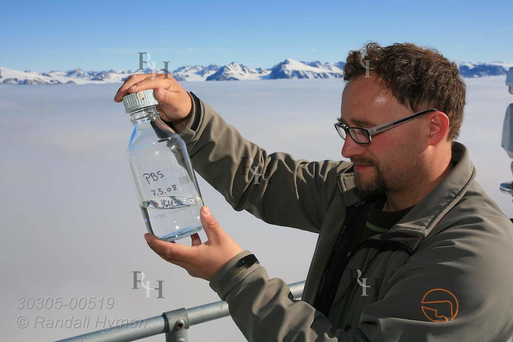 Microbiologist Runar Thyrhaug samples atmospheric bacteria using water-filtered vacuum cleaners atop Zeppelin Station; Ny-Alesund, Svalbard, Norway.