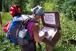 A hiker signs the trail register for the Byers Creek Trail near Byers Peak in the Byers Peak Wilderness located in the Arapaho National Forest in Colorado. Signing trail registers give land managers information on the number of people using a trail and also information should a hiker be reported as overdue from hike. The Byers Peak Wilderness encompasses 8,801 acres in the Arapaho and Roosevelt National Forests near Winter Park, Colorado. The wilderness area was established in 1993. The wilderness area and the 12,804 foot peak are named after William N. Byers, founder of Colorado's first newspaper, the Rocky Mountain News.