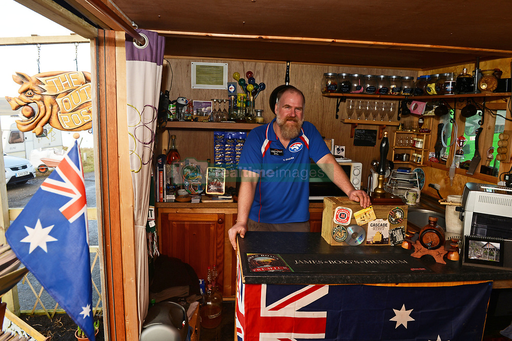 EXCLUSIVE: An Australian man has created his own Outback outpost 11,000 miles from home on the Shetland Islands – and he even has WALLABIES. Tasmanian Dave Kok, 42, has built his own Aussie oasis on the Scottish archipelago after deciding to settle there when he was travelling Europe. Now Dave lives with his Shetland native wife Louise, 38, and two daughters Caitlin, 11, and Ruby, aged four. Social care worker Dave came to the islands in the late 90s and since 2016 has been building his own watering hole choc-full of Australiana on the island of Burra. Dave's place 'The Outpost' is a renovated wooden porta cabin filled with Tasmanian beers, Tim Tams, books on bush craft and Aussie Rules sporting memorabilia. Locals use the Outpost as their local bar and meeting place, as the nearest pub or café is three bridges and three islands away. And visitors can now enjoy the Outpost's wallabies Ned and Kelly who David brought to the island this winter. Based on the Shetland Islands latitude the marsupials could be the most northerly of their species anywhere on the planet. Dave said visiting Australians are often surprised to find the antipodean paradise in such a remote location. 16 Feb 2018 Pictured: Pic from Dave Donaldson/ Magnus News Agency. Pic shows David Kok inside the Aussie-themed Outpost in the Shetland Islands. An Australian man has created his own Outback outpost 11,000 miles from home on the Shetland Islands – and he even has WALLABIES. Tasmanian David Kok, 42, has built his own Aussie oasis on the Scottish archipelago after deciding to settle there when he was travelling Europe. Now David lives with his Shetland native wife Louise and two daughters Caitlin, 11, and Ruby, aged four. Social care worker David came to the islands in the late 90s and has built his own watering hole choc-full of Australiana on the island of Burra. David's place 'The Outpost' is a renovated wooden porta cabin filled with Tasmanian beers, Tim Tams, books on bush craf