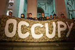 © licensed to London News Pictures. London, UK 12/05/2012. Occupy London protesters posing with a banner as the protesters occupy the area outside the Bank of England and a small group keeps resisting the police, tonight (12/05/12). Photo credit: Tolga Akmen/LNP