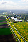 Nederland, Flevoland, Lelystad, 07-05-2015; rijksweg A6 tussen Lelystad en Almere. Voorjaar met de gele bloemen van het raapzaad. Rechts Oostvaardersplassen.<br /> Motorway through the new polder and the yellow flowers of rapeseed in spring.<br /> <br /> luchtfoto (toeslag op standard tarieven);<br /> aerial photo (additional fee required);<br /> copyright foto/photo Siebe Swart