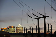 As evening light fades, bright light from the electricity-hungry Canary Wharf docklands development is supplied by the voltage from electricity cables and supporting struts at an east London sub-station, England. A network of 110 miles of cables have stretched across 542 'L6' pylons across England's Kent countryside, from the coal-fired power station at Dungeness to this location, carrying 40,000 Volts along this network of aluminium cables to power some of London's high supply demands. Insatiable appetites for energy means electricity is now an expensive commodity after climbing oil prices doubled electricity utility bills for some domestic users.