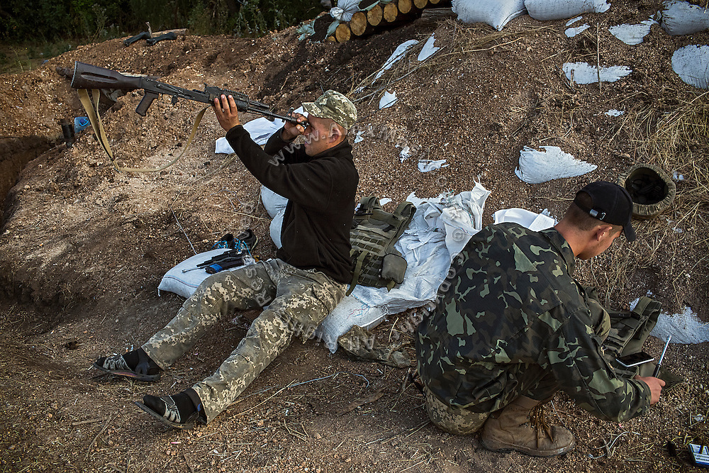 In the morning, two soldiers are cleaning up their rifles next to trenches on the frontline of Hranitne, near Mariupol, southeast Ukraine.