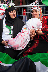 "London, August 23rd 2014. Two women hold a ""bloodstained"" bundle of cloth symbolising a dead baby as hundreds of protesters outside Downing Street demand that Britain stops arming Israel."