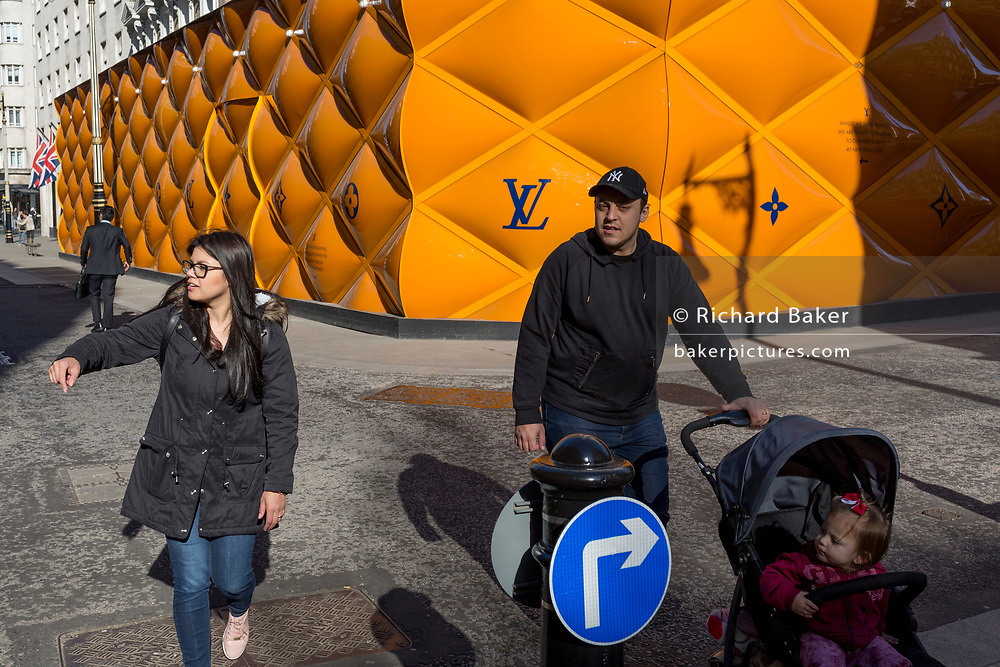 A young family walks opposite the temporary renovation hoarding of luxury brand Louis Vuitton in New Bond Street, on 25th February 2019, in London, England.