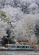 © Licensed to London News Pictures. 12/12/2012. Henley, UK A narrow boat surrounded by frosty trees on the River Thames. Frosty weather around Henley today 12 December 2012. Fog and ice has caused disruption around the country.  Photo credit : Stephen Simpson/LNP