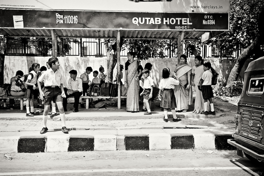 Indian children, in school uniforms, in New Delhi wait with their parents for the school bus. Black and white using Silver Efex Pro.
