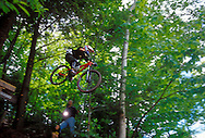 A mountain biker is a blur of motion as he sails through the trees after hitting a jump during  the Superior Bike Fest competition at Marquette Mountain in Marquette, Mich.