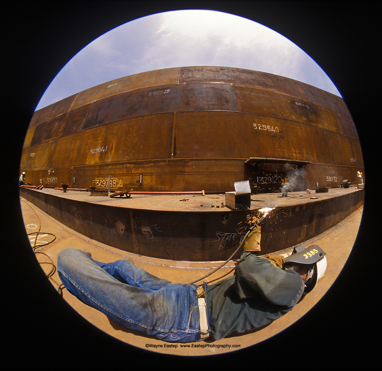 Afghan welder working on a new oil storage tank at the Texaco refinery in Kuwait.