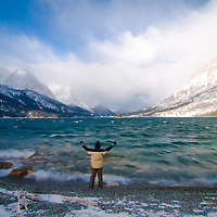 tony bynum stands with arms raised on shore of saint mary's lake wind blowing waves crashing