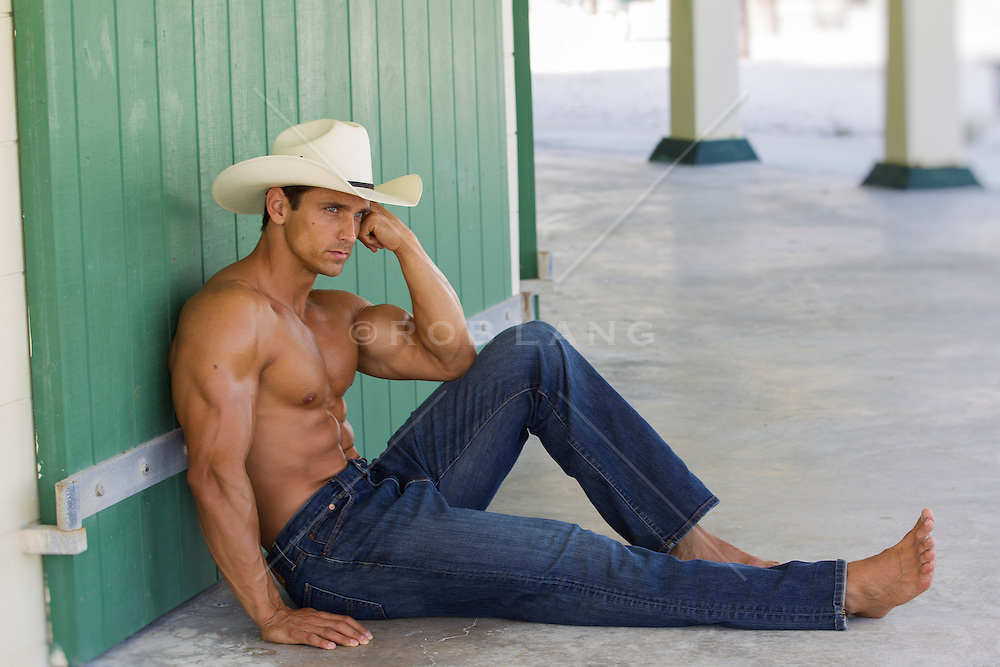 muscular shirtless cowboy against a wall wearing only a cowboy hat and jeans