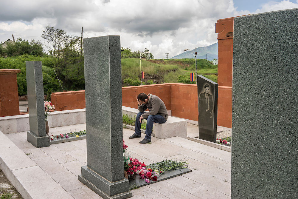A man cries at the grave of a fighter killed in the 1990s war between Armenia and Azerbaijan following a ceremony commemorating both the victory over Nazi Germany in the Second World War as well as the fall of the strategic town of Shushi to Armenian forces on Monday, May 9, 2016 in Stepanakert, Nagorno-Karabakh.
